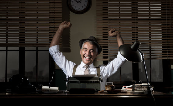 Cheerful successful reporter working at office desk with fists raised.